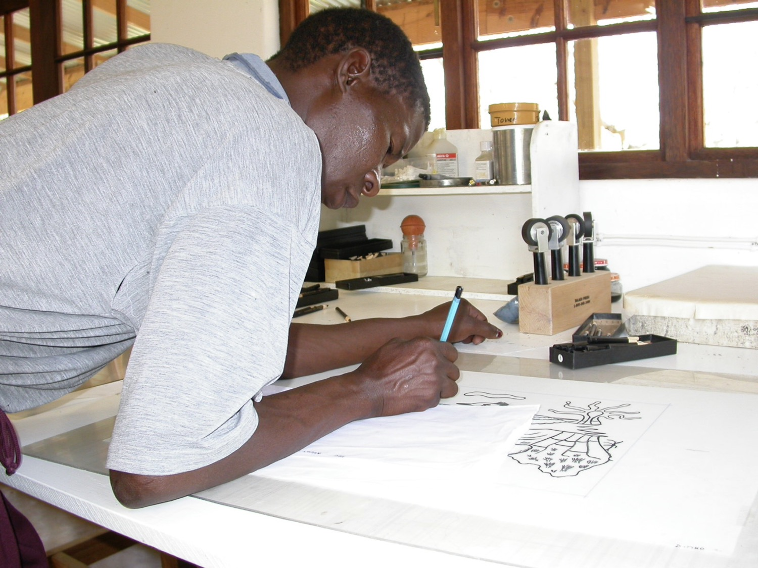 Artist Ditiro Makwena drawing on grained film for a lithograph of his at The Artists' Press.