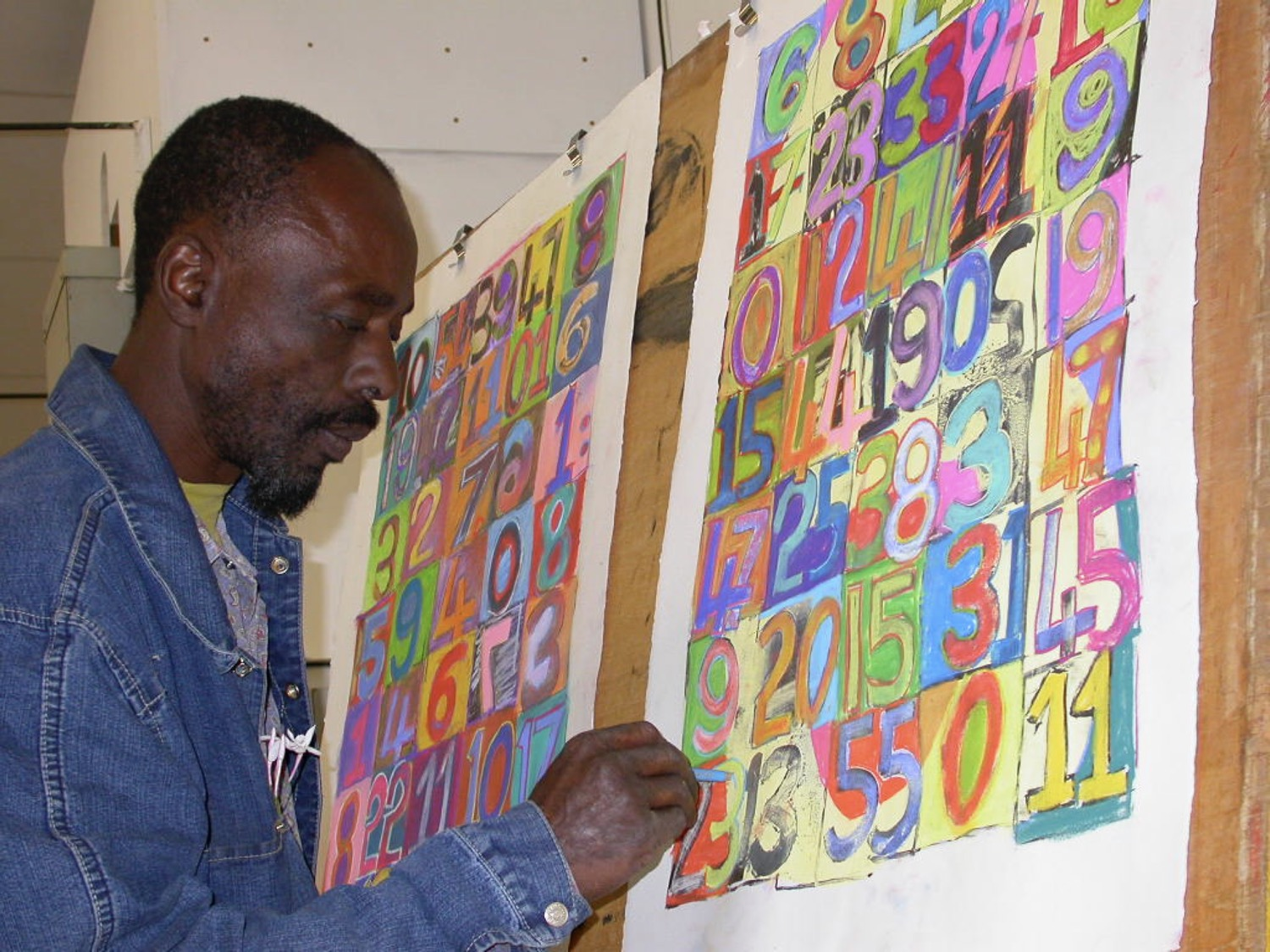 Dumisani Mabaso drawing onto two of his brightly coloured lithographs at The Artists' Press