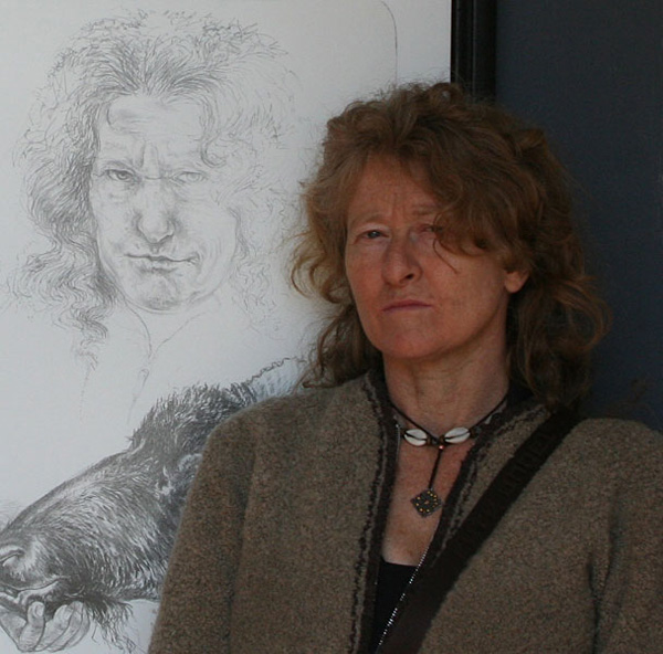 Photograph of Diane Victor standing in front of her self-portrait lithograph