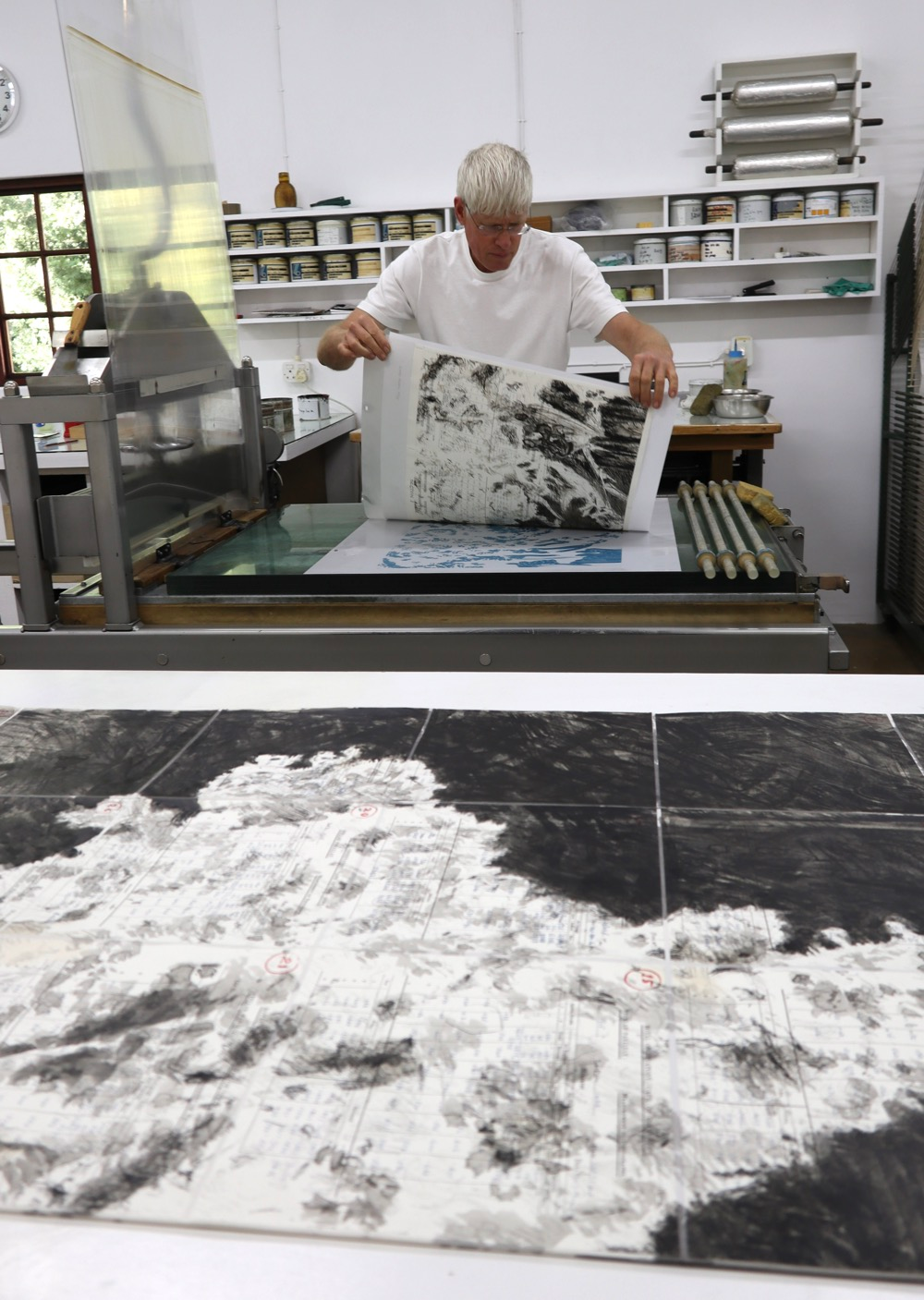 Mark Attwood hand printing a limited edition lithograph by William Kentridge on a lithography press at The Artists' Press.